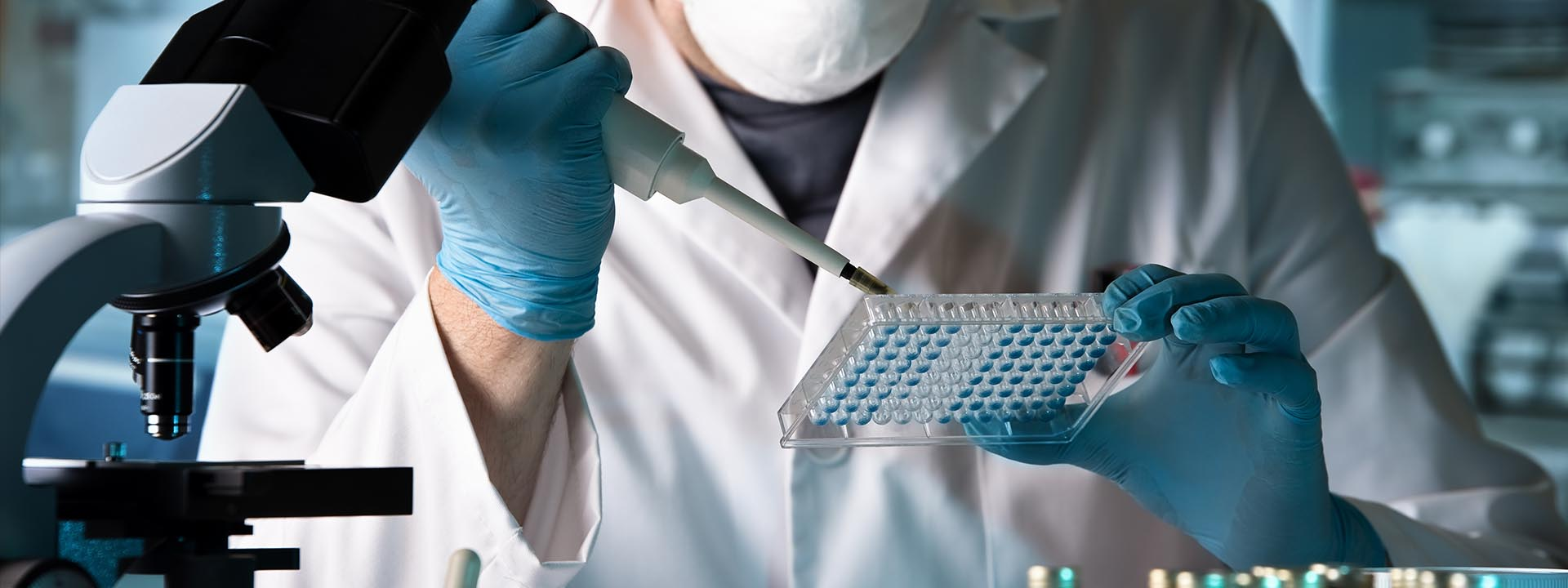 Life science researcher performing ELISA test pipette onto plate