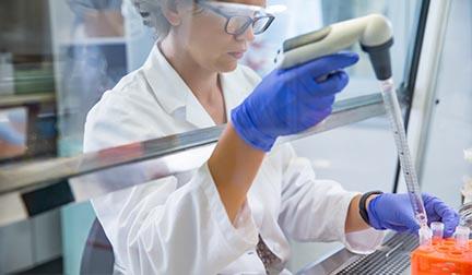 female scientist working under hood with serum free media